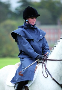 Shires raincoat. Mine is black or perhaps very dark navy. There are straps to keep it over your legs when riding. I am very (over) excited by it!